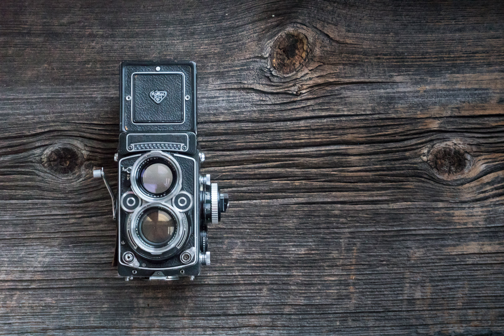 VIntage Rolleiflex medium format film camera photographed on barn board.